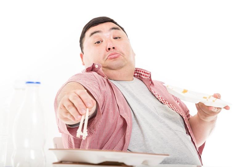 食べ過ぎで太った男性